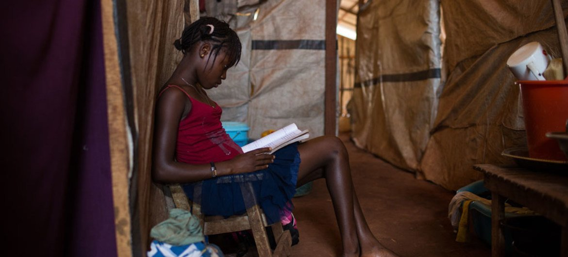 A 14 year-old girl reads a book beneath a makeshift shelter at the Grand Séminaire Saint Marc de Bimbo site for internally displaced people, in Bangui, Central African Republic.