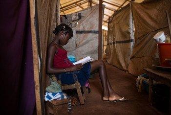 Une jeune fille lit un livre dans un abri de fortune dans un camp de déplacés à Bangui, en République centrafricaine (archives). Photo UNICEF/Tanya Bindra