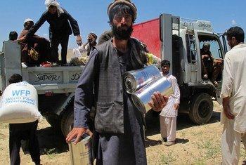 مواطنون أفغان عائدون من باكستان يتلقون مساعدات غذائية.