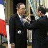 Secretary-General Ban Ki-moon (left) receives the insignia of the <em>Grand Officier de la Légion d'honneur</em> (the Grand Officer of the Legion of Honour) from President François Hollande of France.