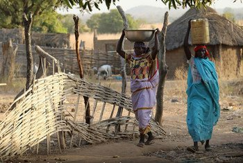 Women in Gordil, Central African Republic (CAR), carry food and water back home as evening descends.