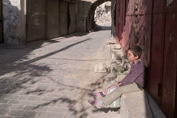 A nine year-old child sits in one of the neighbourhoods in the old city of Aleppo, Syria, holding his jerry can, looking for drinking water.