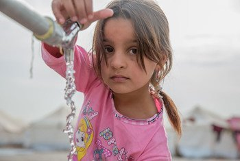 On 15 November 2016, a young girl from Mosul takes water from a tap stand at a UNICEF-supported Temporary Learning Space in Hassan Sham Displacement Camp, Ninewa Governorate.