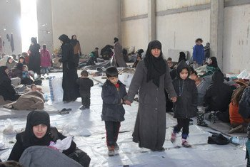 Сирийская женщина с  детьми. Они  недавно бежали из восточных кварталом Алеппо и нашли приют в одном из промышленных районов на западе. Фото УВКБ