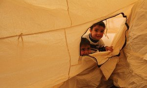 Two young Iraqi boys, their family displaced by the fighting in Mosul, peek out through the zipper of their tent at Hasansham camp, as UNHCR delivers cold weather supplies, including warm blankets and stoves.