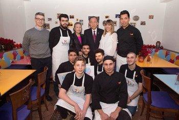 El Secretario General  Ban Ki-moon posa con los refugiados que trabajan en el restaurante Habibi Hawara en Viena. Foto: ONU /Eskinder Debebe