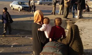 A woman and her children wait for transportation in Aleppo, Syria.