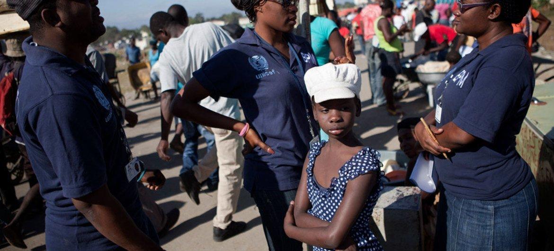 Une fille attend avec des officiers de la Brigade de protection des mineurs (BPM) de la Police haîtienne dans la ville de Ouanaminthe, située près de la frontière nord-est avec la République dominicaine.La BPM est un partenaire de l'UNICEF dans la lutte contre la traite des enfants.