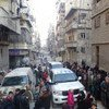 Displaced Aleppo, Syria, residents wait in line to receive food distributed by the World Food Programme.