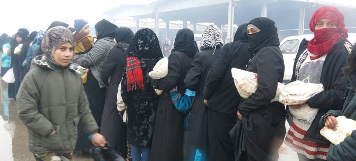 Exodus from eastern Aleppo city: Women line up at a temporary shelter in Al-Mahalej, Syria, to receive bread and hot meals. Many say they lived under constant shelling and bombardment.