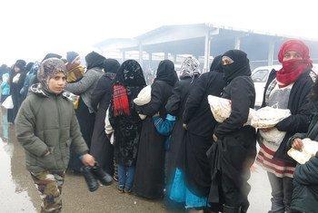Exode depuis les quartiers est d'Alep: des femmes font la queue dans un abri temporaire à Al-Mahalej, Syrie, afin de recevoir du pain et un repas chaud. Beaucoup d'entre elles disent avoir vécu sur des tirs et bombardements constants.