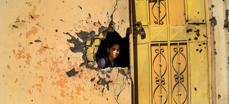 Msichana akichungulia akiwa ndani ya nyumba iliyoharibiwa katika mapigano ya Ramadi, Anbar, Iraq.