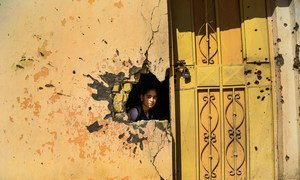 A young girl looks through a hole in the wall from damage from conflict in a school in Ramadi, Anbar Governorate, Iraq. Photo: UNICEF/Wathiq Khuzaie