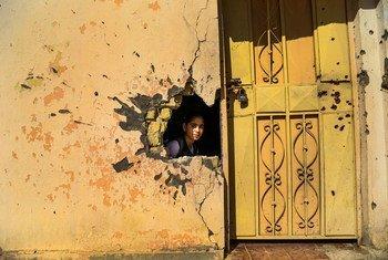Une jeune fille regarde à travers le trou d'un mur endommagé par le conflit dans une école de Ramadi, dans le Gouvernorat d'Anbar, en Iraq. UNICEF/Wathiq Khuzaie
