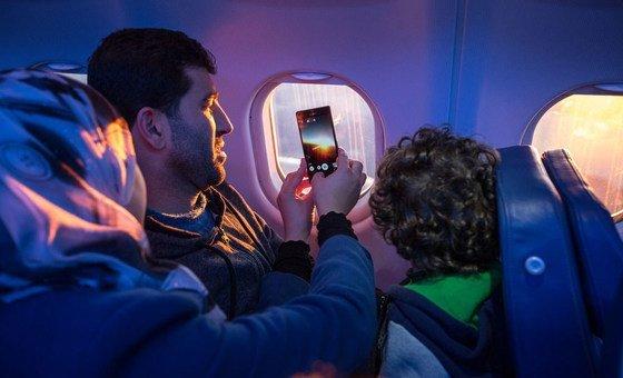 أسرة مهاجرة تلتقط صورة من الطائرة التي تقلها في رحلة الهجرة.
