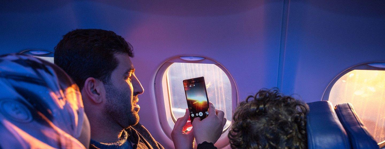 Una familia mira por la ventana del avión y toma fotos mientras viajan a su nuevo hogar.