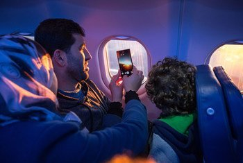 A migrant family looks out the window and take pictures as they undertake their journey for resettling.