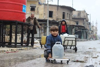 सीरिया के पूर्वी अलेप्पो शहर में कुछ लड़के, यूनीसेफ़ समर्थित जल निकायों से पानी इकट्ठा कर रहे हैं.