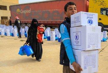 Des familles transportent des provisions depuis un point de distribution situé dans la partie est de Mossoul, en Iraq.