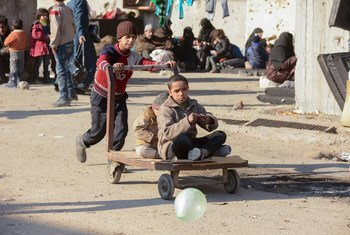 Children at a shelter in Jibreen, Aleppo, Syria, play with a cart.