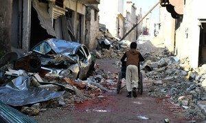 A boy pulls a wheelchair along a debris strewn street in Al-Mashatiyeh neighbourhood of eastern Aleppo, Syria.