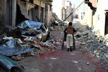 Un niño sirio empuja una silla de ruedas en el este de Alepo. Foto: ACNUR/Bassam Diab
