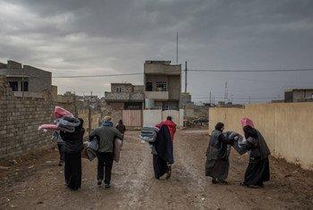 Des personnes ayant reçu des couvertures du HCR rentrent chez elles après une distribution d'aide dans une zone libérée de l'est de Mossoul, en Iraq.