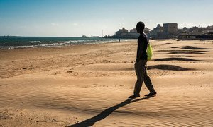 A youngster walks onto the beach during outing from a reception centre that doubles as a lodging station for unaccompanied minors in Pozzallo, Sicily.