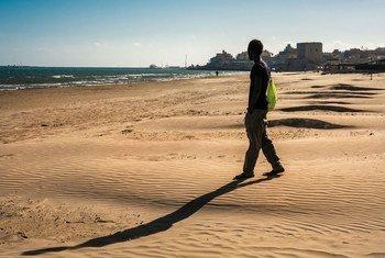 شاب لاجئ يتنزه على الشاطئ بالقرب من مركز استقبال للاجئين ومقر لإقامة القصر غير المصحوبين بذويهم في بوزالو، صقلية.