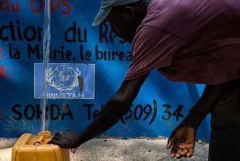 A resident of the town of Merger, an hour outside of Port au Prince, Haiti, fills his container at the water capture and distribution project.
