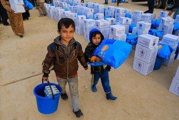 Айман (слева) и Халид (справа)   несут  товары, полученные  в центре по  распределению помощи в восточной части города Мосула в Ираке. Фото ЮНИСЕФ