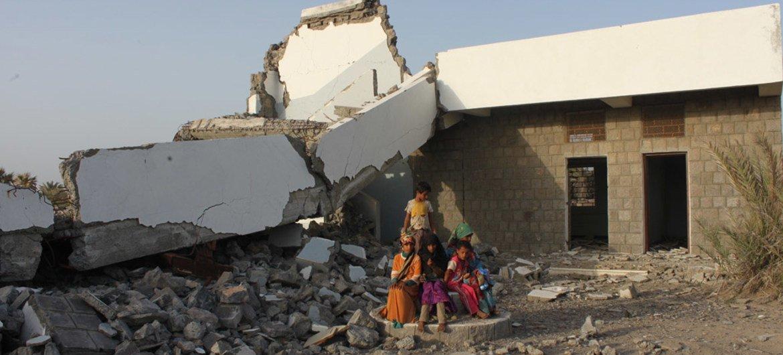 أطفال يجلسون أمام مدرسة تضررت بشدة في الصراع الدائر في اليمن
