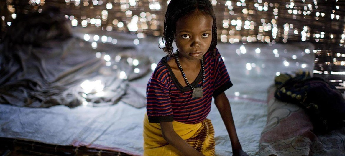 Fatima, 7, sits on a bed in her home in Afar region, Ethiopia. She was subjected to FGM/C when she was 1 year old.