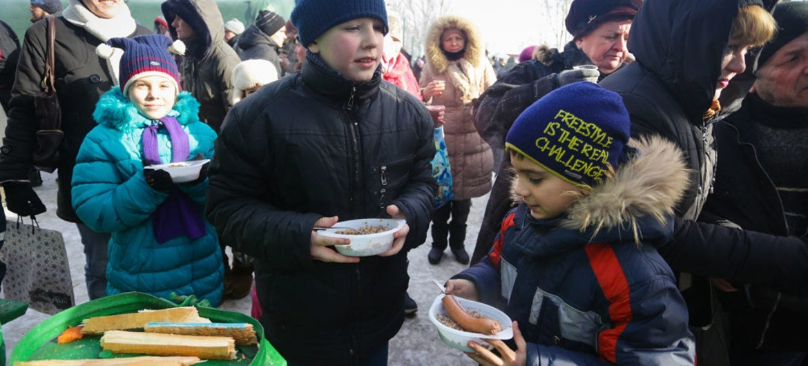 On 1 February 2017, children eat a hot meal at a heated emergency shelter in freezing cold Avdiivka, Ukraine, following intense fighting at the end of January 2017.