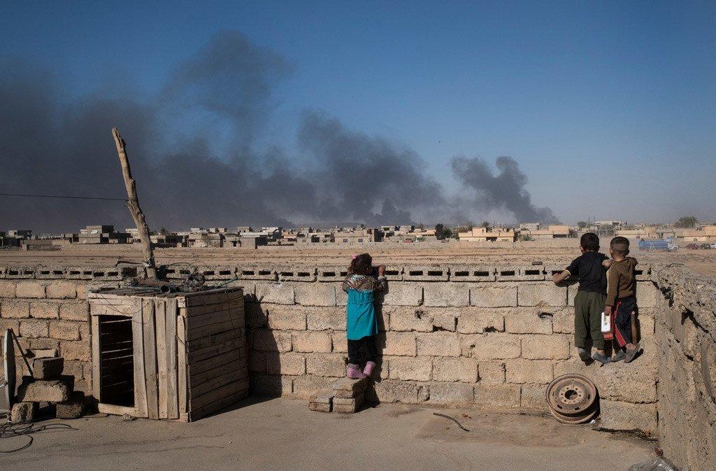 Du haut du toit de leur maison, des enfants regardent les nuages de fumée des puits de pétrole qui ont été incendiés par Daech lorsqu'ils ont fui Qayyarah, une ville au sud de Mossoul, en Iraq (photo d'archives).