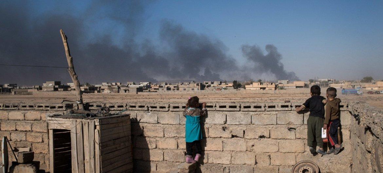 أطفال ينظرون من وراء جدار على سطح منزلهم إلى  سحب الدخان من آبار النفط التي أحرقها تنظيم داعش عندما فروا من بلدة في جنوب الموصل. (من الأرشيف)