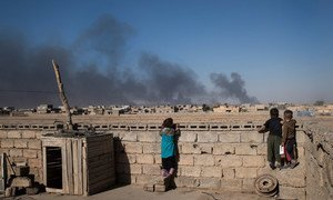 Children look over the wall on the roof of their house at clouds of smoke from oil wells which were set on fire by ISIL when they fled Qayyarah, a town south of Mosul. (file)