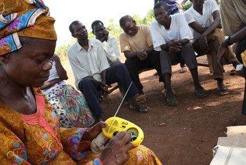 Des résidents du site pour déplacés de Sangari, en République centrafricaine, écoute une radio communautaire qui encourage la tolérance entre les communautés. Photo OCHA/Gemma Cortes