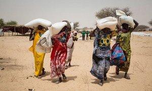 Des personnes vivant dans le camp de déplacés de Melia, au lac Tchad, reçoivent des vivres du Programme alimentaire mondial (PAM). La plupart des personnes déplacées viennent des îles du lac Tchad, qui ont été abandonnées en raison de l'insécurité.