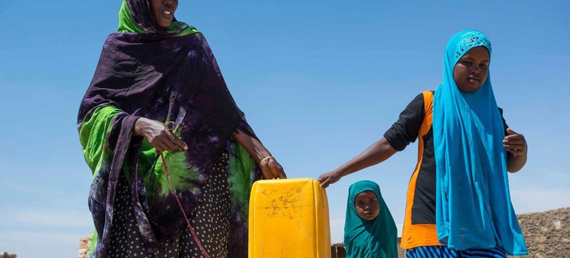 A resident of Rabaable village in Somalia fetches water with the help of her daughters. The villages well was recently rehabilitated by UNICEF.