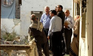 In Yemen, Stephen O'Brien, Under-Secretary-General for Humanitarian Affairs (left facing camera) talks with local residents outside damaged building in Aden.