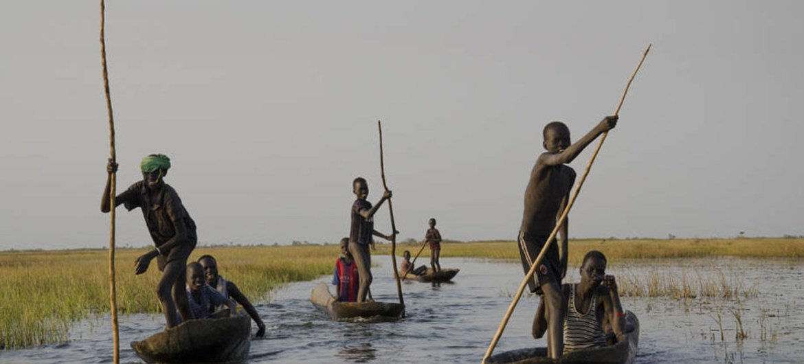 Young boys head home after fishing for a day in the swamps of Nyal, South Sudan.