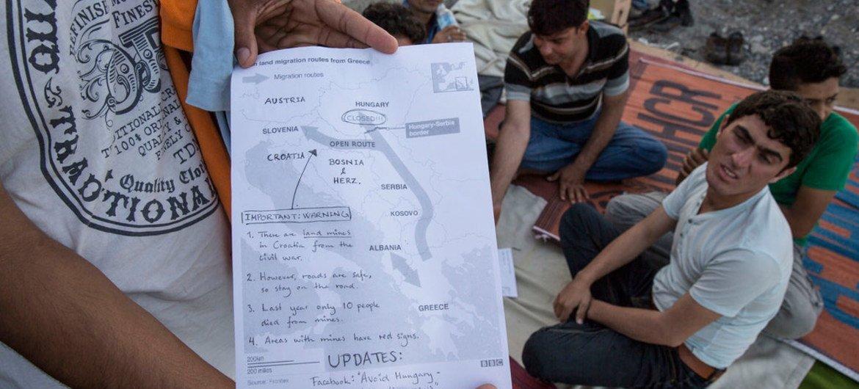 Пакистанские мигранты в Греции рассматривают карту с информацией о закрытии  границы с Венгрией  и предложениями продвигаться  через Хорватию.