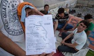 Des migrants pakistanais à Kos, en Grèce, montrent une carte avec des informations sur la fermeture de la frontière hongroise et suggérant de passer par la Croatie. Photo OIM