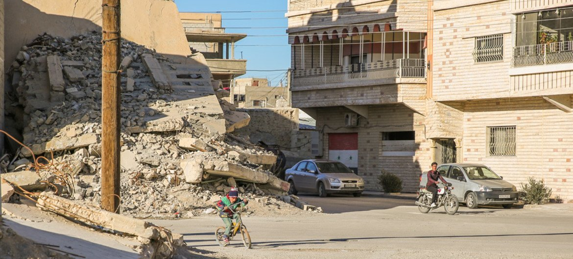 A boy cycles past the rubble of a destroyed house in Qara, where fighting erupted in 2014, dragging the town into the brutal Syrian conflict.