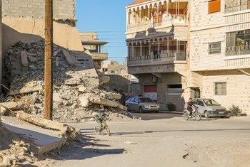 Un niño en bicicleta pasa frente a las ruinas de una casa destruida por la violencia en Qara, Siria. Foto: ACNUR/Qusai Alazroni