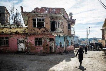Residentes de Silvania, una ciudad en la provincia de Diyarbakir en el sudeste de Turquía, caminan por las calles llenas de casas baleadas.