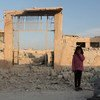 Una niña Siria posa en frente de su escuela destruida por la guerra en Idlib.