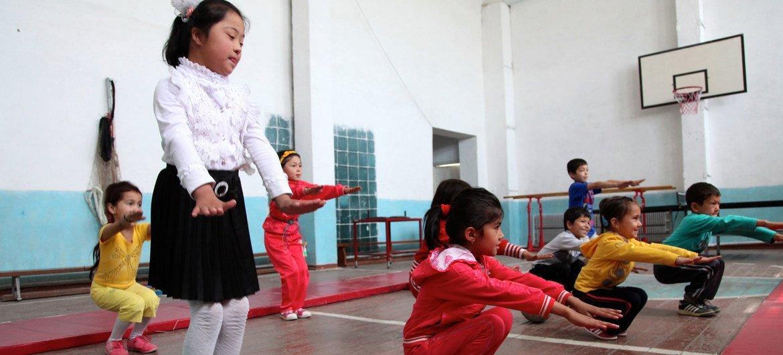 一名乌兹别克斯坦儿童与健康儿童一道参加体育活动。