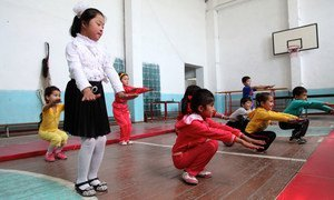 Children doing physical exercises in a school gym in Uzbekistan, among them a child affected by down syndrome.